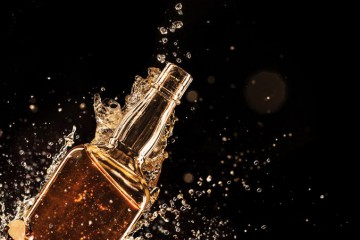 21909187 - isolated shot of whiskey with splash on black background