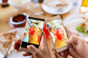 81770291 - hands with drinks on smartphones at restaurant