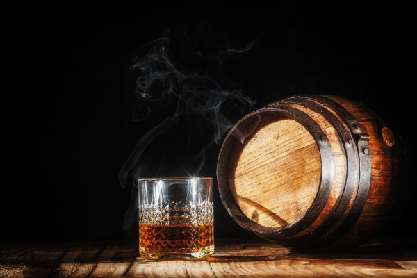 35851410 - glass of alcohol and smoking noble cigar on a black background